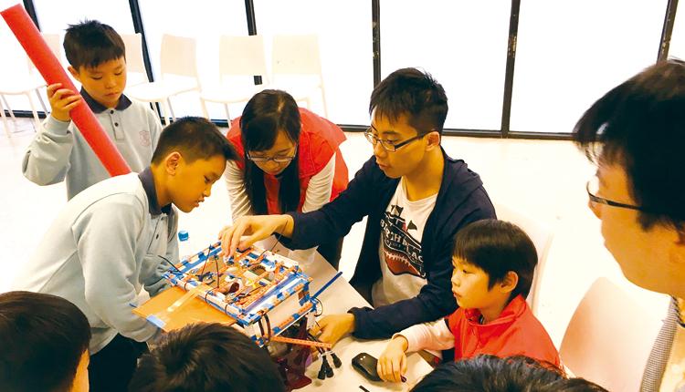 學生在導師的指導下,調整水底機械人,為賽前作最後準備。