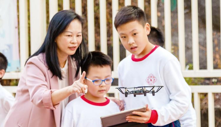 學生利用平板電腦操控無人機進行航空拍攝。