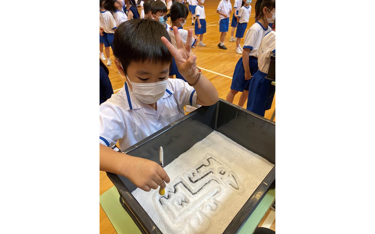 同學在藝術聯展中打中國鼓及畫沙畫。