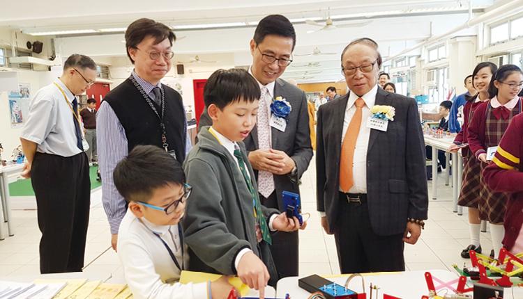 學生為教育局楊潤雄局長及何德心副校監介紹在常識課堂裝嵌的機械人。